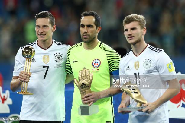 Timo Werner of Germany poses with the golden boot Julian Draxler of Germany the golden ball and Claudio Bravo of Chile the golden glove at the end of...