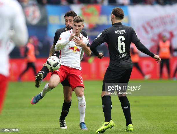 Timo Werner of Leipzig is attacked by Dominic Maroh and Marco Hoeger of Koeln during the Bundesliga match between RB Leipzig and 1 FC Koeln at Red...