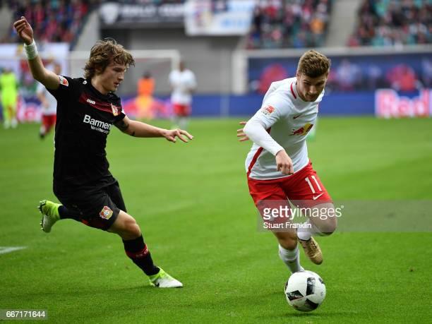 Timo Werner of Leipzig is challenged by Julian Baumgartlinger of Leverkusen during the Bundesliga match between RB Leipzig and Bayer 04 Leverkusen at...
