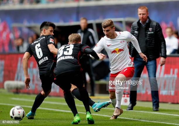 Timo Werner of RB Leipzig is challenged by Alfredo Morales and Florent Hadergjonaj of FC Ingolstadt 04 during the Bundesliga match between RB Leipzig...
