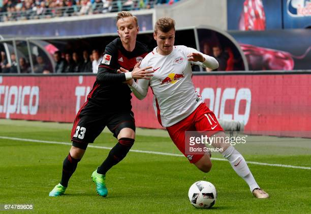 Timo Werner of RB Leipzig is challenged by Florent Hadergjonaj of FC Ingolstadt 04 during the Bundesliga match between RB Leipzig and FC Ingolstadt...
