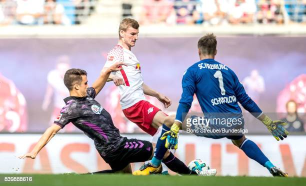 Timo Werner of RB Leipzig is challenged by MarcOliver Kempf of SC Freiburg and goalkeeper Alexander Schwolow of SC Freiburg during the Bundesliga...