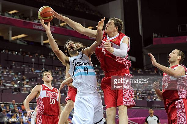Timofey Mozgov of Russia blocks Luis Scola of Argentina during the Men's Basketball bronze medal game between Russia and Argentina on Day 16 of the...