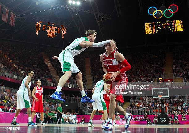 Timofey Mozgov of Russia receives an arm to the head as he looks to shoot against Tiago Splitter of Brazil in the second half during the Men's...