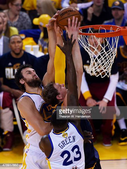 Timofey Mozgov of the Cleveland Cavaliers dunks against Andrew Bogut and Draymond Green of the Golden State Warriors in the first quarter during Game...