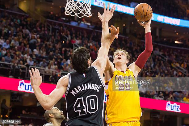 Timofey Mozgov of the Cleveland Cavaliers shoots over Boban Marjanovic of the San Antonio Spurs during the first half at Quicken Loans Arena on...