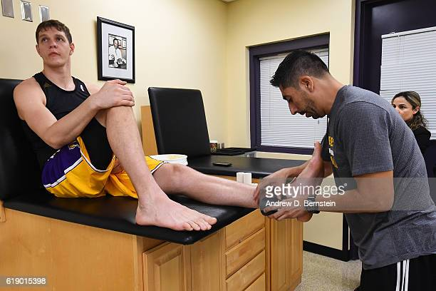 Timofey Mozgov of the Los Angeles Lakers gets taped up from trainer Marco Nunez before the game against the Houston Rockets on October 26 2016 at...