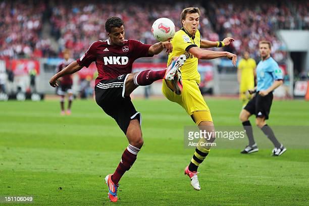 Timothy Chandler of Nuernberg is challenged by Kevin Grosskreutz of Dortmund during the Bundesliga match between 1 FC Nuernberg and Borussia Dortmund...