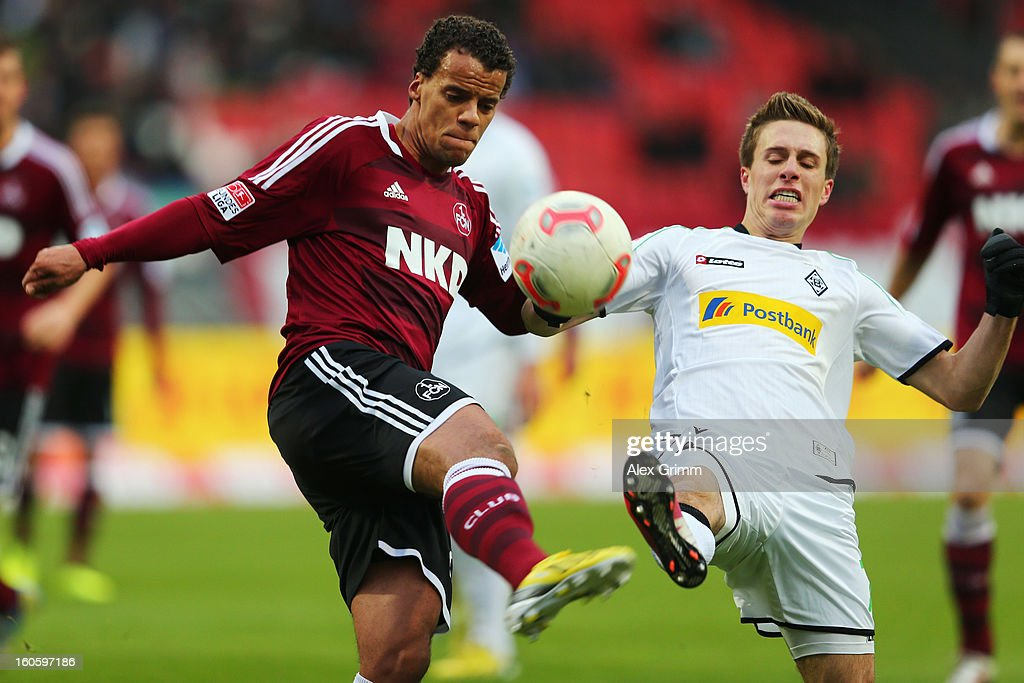 Timothy Chandler (L) of Nuernberg is challenged by Patrick Herrmann of Moenchengladbach during the Bundesliga match between 1. FC Nuernberg and VfL Borussia Moenchengladbach at Easy Credit Stadium on February 3, 2013 in Nuremberg, Germany.