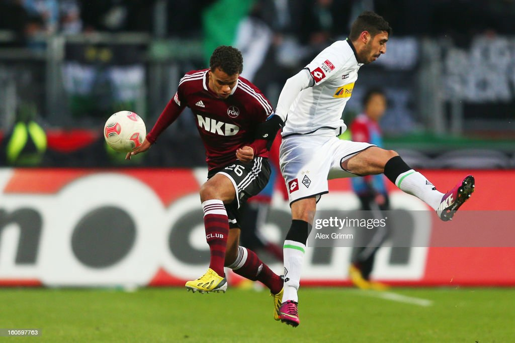 Timothy Chandler (L) of Nuernberg is challenged by Tolga Cigerci of Moenchengladbach during the Bundesliga match between 1. FC Nuernberg and VfL Borussia Moenchengladbach at Easy Credit Stadium on February 3, 2013 in Nuremberg, Germany.