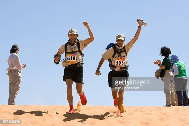 Timothy Fears of USA and Thomas Dever of USA react as they run to the finish line during the sixth and final stage of the 22nd Marathon des Sables...