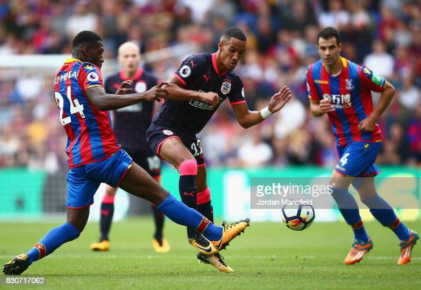 Timothy FosuMensah of Crystal Palace and Tom Ince of Huddersfield Town battle for possession during the Premier League match between Crystal Palace...