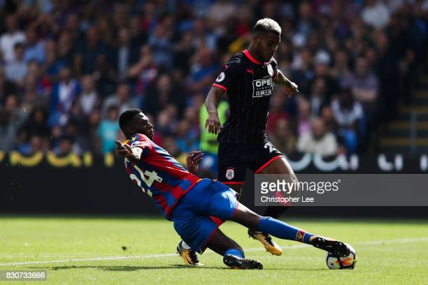 Timothy FosuMensah of Crystal Palace tackles Steve Mounie of Huddersfield Town during the Premier League match between Crystal Palace and...