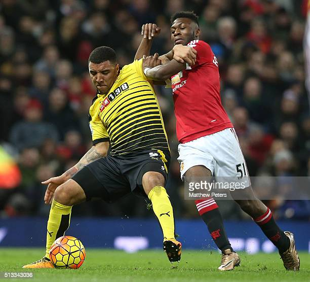 Timothy FosuMensah of Manchester United in action with Troy Deeney of Watford during the Barclays Premier League match between Manchester United and...