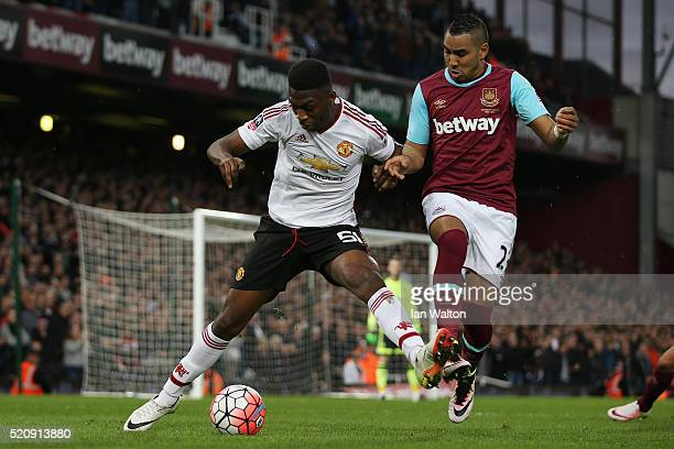 Timothy FosuMensah of Manchester United is challenged by Dimitri Payet of West Ham United during The Emirates FA Cup sixth round replay between West...