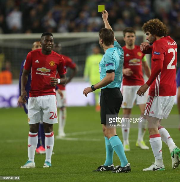 Timothy FosuMensah of Manchester United speaks to Timothy FosuMensah is booked by referee Felix Brych during the UEFA Europa League quarter final...
