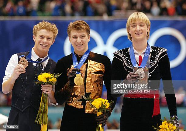 Timothy Goebel of the US Russians Alexei Yagudin and Evgeny Plushenko jubilate on the podium at the end of the men's free program at the Olympic Ice...