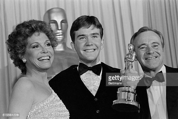 Timothy Hutton holds up his Oscar with presenters Mary Tyler Moore and Jack Lemmon after he was awarded the Best Performance by an Actor in a...