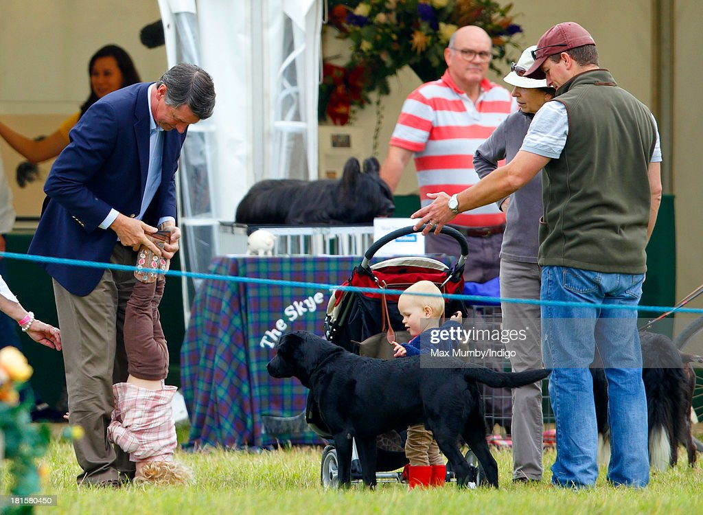 Timothy Laurence plays with Savannah Phillips as Isla Phillips, Peter Phillips and Princess Anne, The Princess Royal look on at the Gatcombe Horse Trials at Gatcombe Park, Minchinhampton on September 22, 2013 in Stroud, England.
