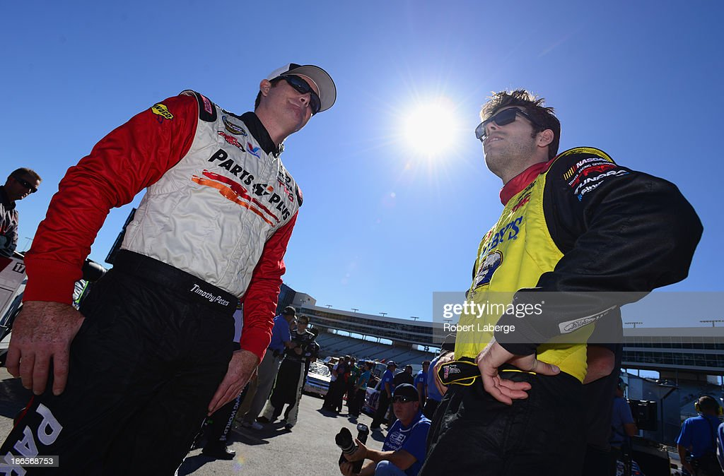 Timothy Peters, driver of the #17 Parts Plus Toyota, talks with John Wes Townley, driver of the #7 Zaxby's Toyota, during qualifying for the NASCAR Camping World Truck Series WinStar World Casino 350k at Texas Motor Speedway on November 1, 2013 in Fort Worth, Texas.