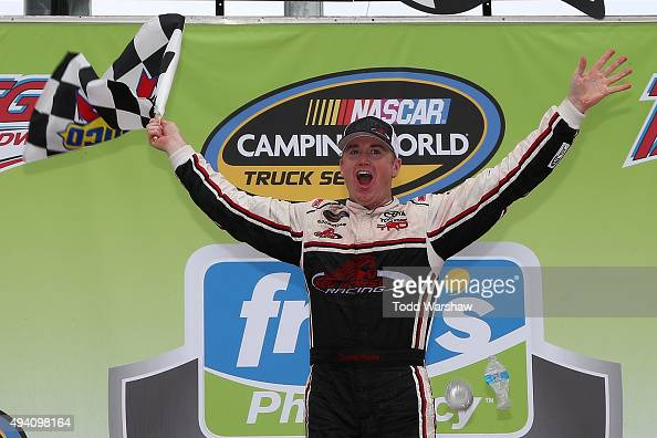 Timothy Peters driver of the Red Horse Racing Toyota celebrates in Victory Lane after winning the NASCAR Camping World Truck Series fred's 250 at...