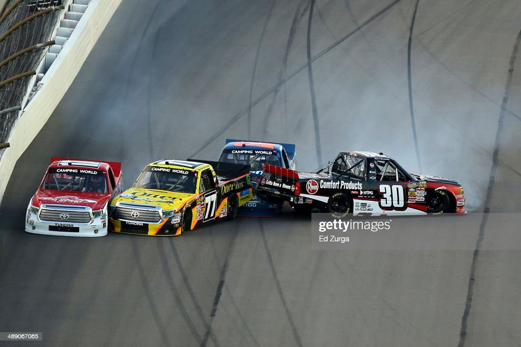 <a gi-track='captionPersonalityLinkClicked' href=/galleries/search?phrase=Timothy+Peters&family=editorial&specificpeople=574872 ng-click='$event.stopPropagation()'>Timothy Peters</a>, driver of the #17 Red Horse Racing Toyota, German Quiroga, driver of the #77 OtterBox Toyota, Spencer Gallagher, driver of the #23 Allegiant Travel Chevrolet, and <a gi-track='captionPersonalityLinkClicked' href=/galleries/search?phrase=Ron+Hornaday+Jr.&family=editorial&specificpeople=4267064 ng-click='$event.stopPropagation()'>Ron Hornaday Jr.</a>, driver of the #30 Rheem Chevrolet, spin out after an incident during the NASCAR Camping World Truck Series SFP 250 at Kansas Speedway on May 9, 2014 in Kansas City, Kansas.
