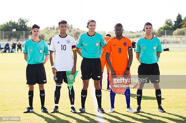 Timothy Tillman of Germany and Leandro Fernandes of Netherlands pose with the referees before during the U18 international friendly match between...