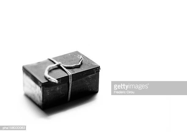 Tin box tied with string, b&w.