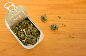 Tin can with high quality marijuana buds on wooden background with copy space right. Hidden drug. Packaged marketed marijuana with a secure method.