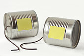 Tin cans phone with broken string and paper note - Communication concept