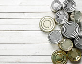 Tin cans with food. On white wooden table.