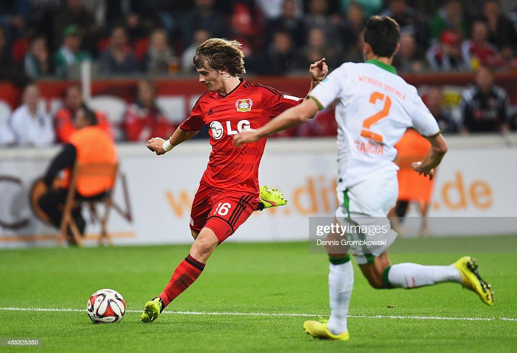 Tin Jedvaj of Bayer Leverkusen shoots past Santiago Garcia of Werder Bremen to score their first goal during the Bundesliga match between Bayer 04...