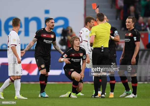 Tin Jedvaj of Leverkusen is shown a yellowred card by referee Daniel Siebert during the Bundesliga match between Bayer 04 Leverkusen and Bayern...
