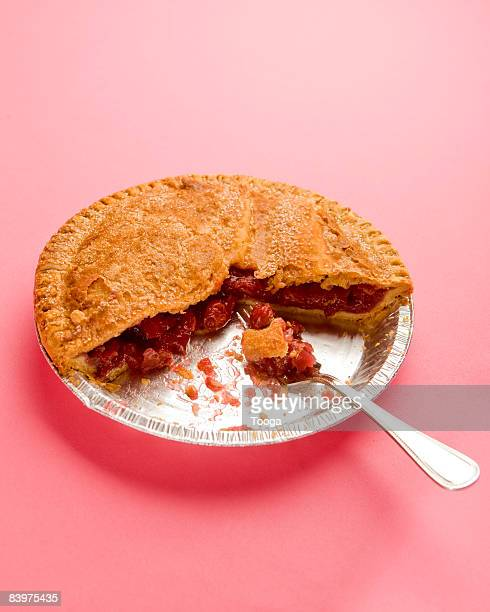 Tin of cherry pie with fork