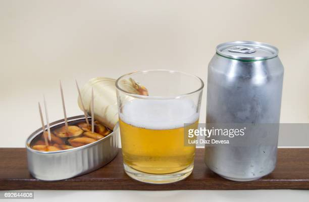 tin of Mussels in spicy sauce, beer Can and glass of beer