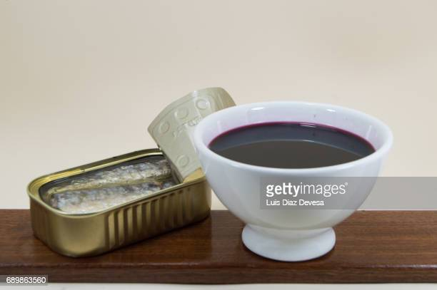 tin of sardines in olive oil and a white earthenware cup of red wine