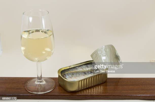 tin of sardines in olive oil and  next to a glass of white wine