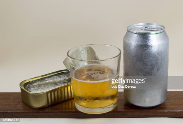 tin of sardines in olive oil, beer Can and glass of beer