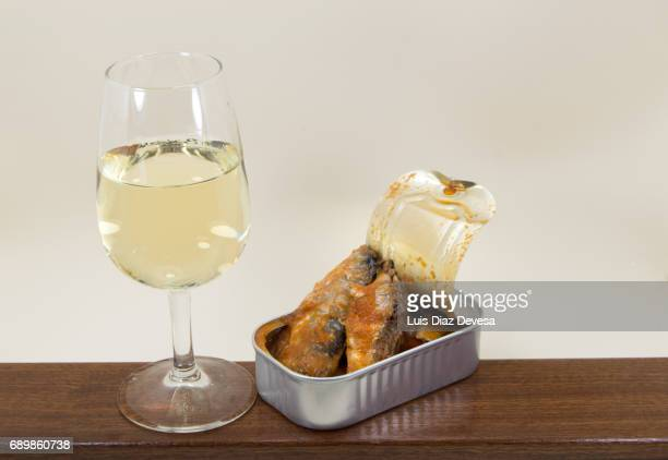 tin of sardines in tomato sauce and  next to a glass of white wine
