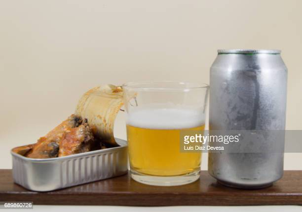 tin of sardines in tomato sauce, beer Can and glass of beer