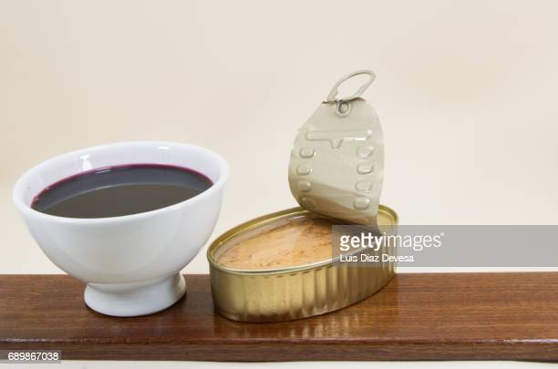tin of tuna in olive oil and and a white earthenware cup of red wine