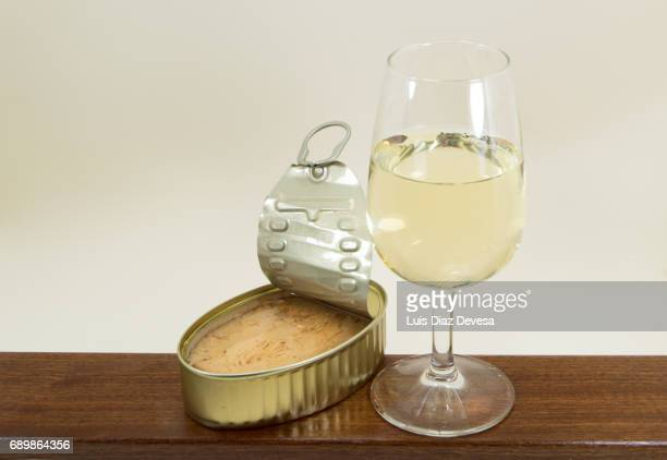 tin of tuna in olive oil and  next to a glass of white wine