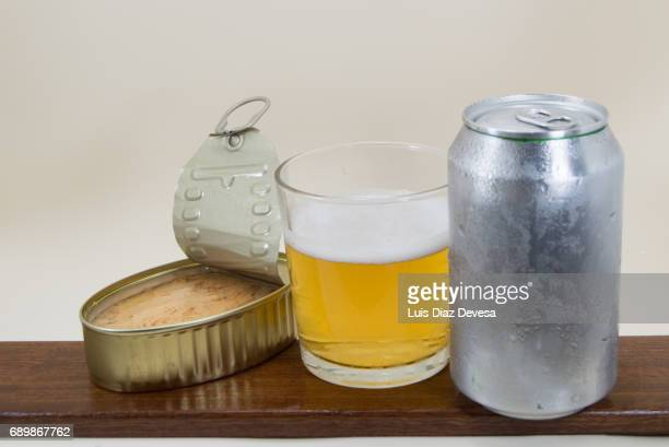 Tin tuna in olive oil, beer Can and glass of beer