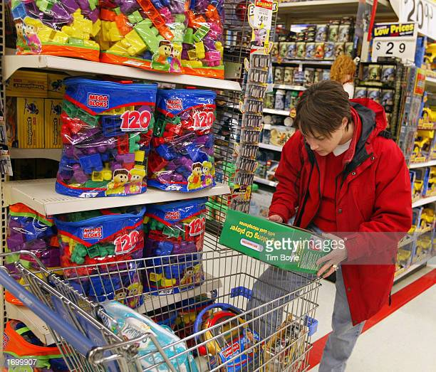 Tina Bellows reads the back of a box while shopping at a WalMart two days before Christmas December 23 2002 in Mount Prospect Illinois WalMart Stores...