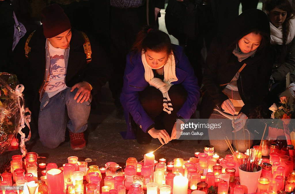 Tina K. (C), elder sister of Jonny K., and family friend Trang Nguyen (R) light candles at a makeshift memorial to Tina's murdered brother following a memorial service for him and other victims of violence in Berlin at Alexanderplatz on November 21, 2012 in Berlin, Germany. Jonny K. died after a group of youths beat him severely in the early hours of October 14 at Alexanderplatz. Investigations are continuing as three of the suspects remain abroad, one in Turkey and two in Greece.