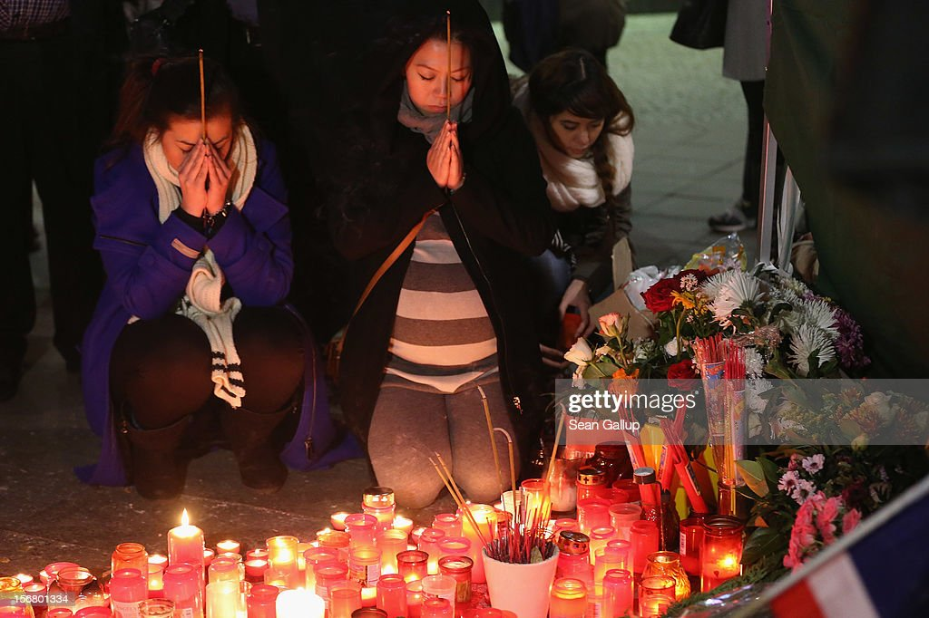 Tina K. (L), elder sister of Jonny K., and family friend Trang Nguyen pray after lighting candles at a makeshift memorial to Tina's murdered brother following a memorial service for him and other victims of violence in Berlin at Alexanderplatz on November 21, 2012 in Berlin, Germany. Jonny K. died after a group of youths beat him severely in the early hours of October 14 at Alexanderplatz. Investigations are continuing as three of the suspects remain abroad, one in Turkey and two in Greece.