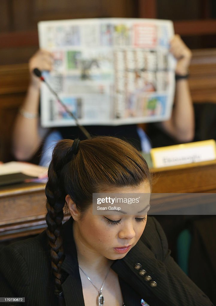 Tina K., sister of victim Jonny K., sits in the courtroom as co-defendant Memet E. covers his face shortly before the continuation of the trial of the six Jonny K. attackers at the Kriminalgericht Moabit court on June 17, 2013 in Berlin, Germany. The six young men are accused of assaulting Jonny K. in front of a bar on Alexanderplatz on October 14, 2012, and beating him so severely that Jonny K. later died of his head injuries. His sister Tina has led a media campaign to draw publicity to the case and the issue of violence in German society.