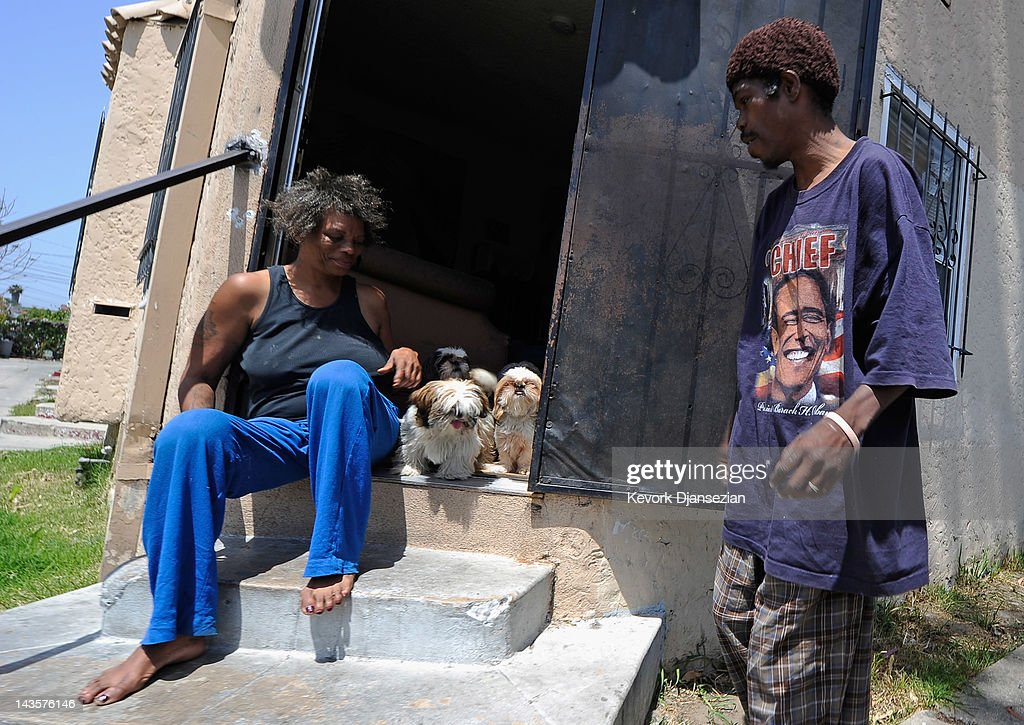 Tina Kelley (L) holds back her four Shitzu dogs as she talks with her husband David Washington after a dispute with a neighbor in South Los Angeles on April 29, 2012 in Los Angeles, California. It's been 20 years since the verdict was handed down in the Rodney King case that sparked the infamous Los Angeles riots.