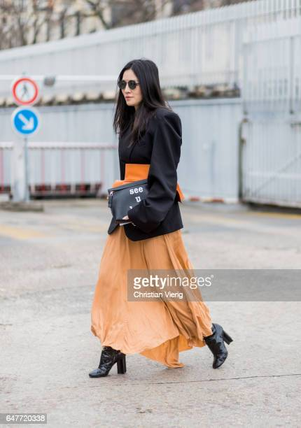Tina Leung wearing black jacket orange shirt Loewe clutch outside Loewe on March 3 2017 in Paris France