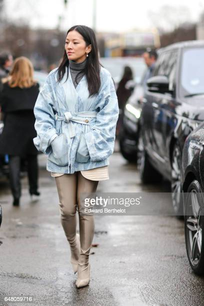 Tina Leung wears a blue kimono coat a gray turtleneck and beige thigh high boots outside the Elie Saab show during Paris Fashion Week Womenswear...